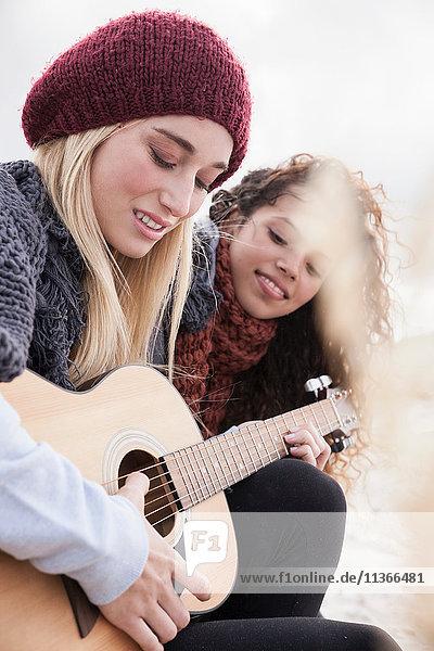Zwei junge Frauen spielen Gitarre am Strand  Western Cape  Südafrika