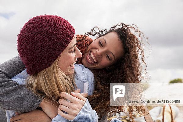 Zwei junge Freundinnen umarmen sich am Strand  Western Cape  Südafrika
