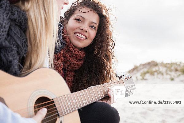 Zwei junge Freundinnen spielen Gitarre am Strand  Western Cape  Südafrika