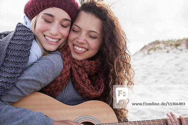 Porträt von zwei jungen Freundinnen beim Gitarrespielen am Strand  Western Cape  Südafrika