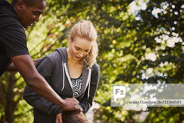 Junge Frau mit Personal Trainerin erklärt Baumstammlift im Park