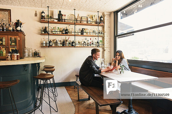 Young couple reading menu in cocktail bar