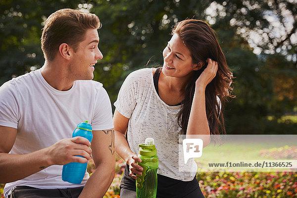 Mann und Frau trainieren im Park  plaudern während einer Wasserpause