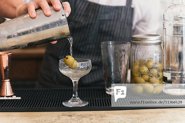 Close up of bartender pouring cocktail at cocktail bar