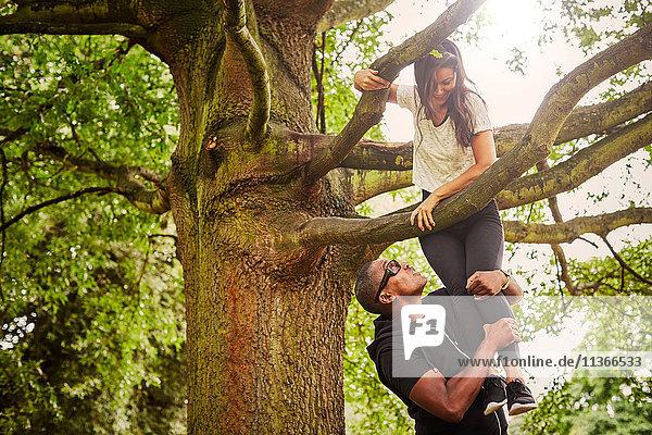 Personal Trainerin hebt Frau zum Klettern auf den Parkbaum