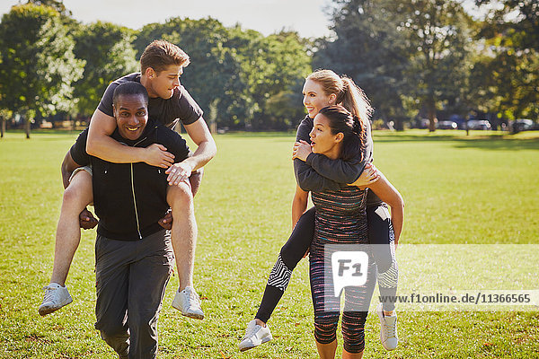Männer und Frauen beim Training im Park  beim Huckepack-Rennen