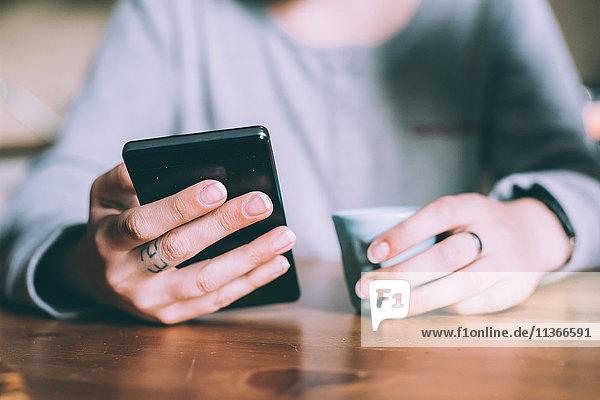 Mittlerer Teil einer jungen Frau am Tisch mit Smartphone und Espresso in der Hand