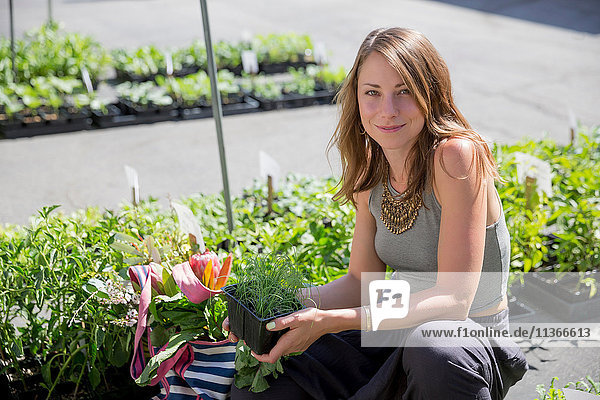 Woman at fruit and vegetable stall holding herb plants