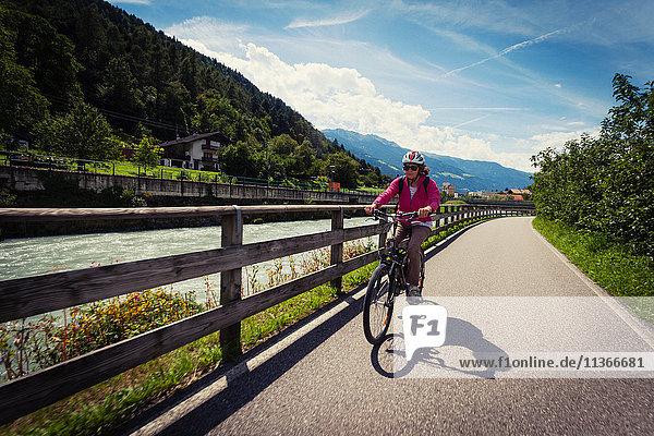 Radfahrerin auf einem Flussweg im Vinschgau  Südtirol  Italien