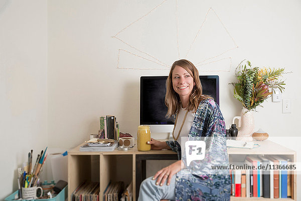 Frau sitzt am Schreibtisch und schaut lächelnd weg