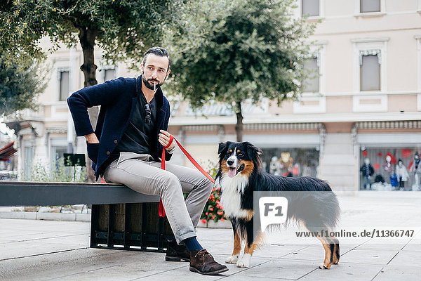 Man with dog smoking cigarette on city street bench