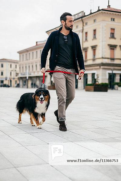 Mid adult man walking dog at city square