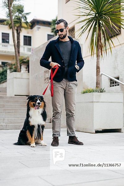 Mid adult man standing with pet dog in city square