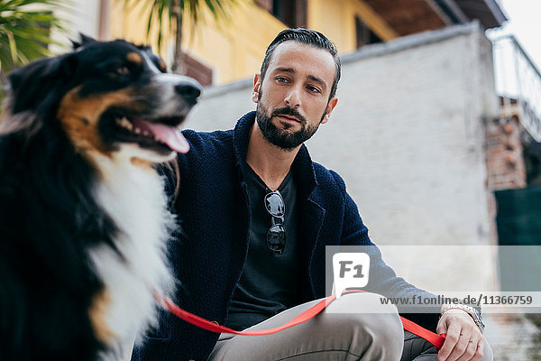 Mid adult man sitting with dog on city step