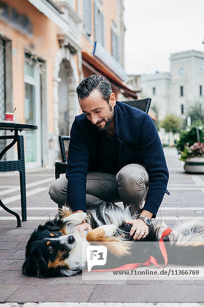 Mid adult man crouching to pet dog in city square
