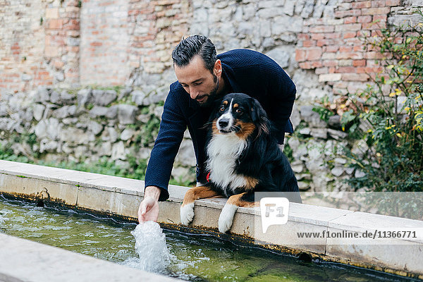 Mid adult man with dog splashing water trough