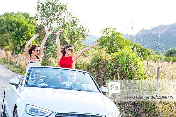 Zwei junge Freundinnen stehen und winken  während sie mit einem Cabrio auf einer Landstraße fahren  Mallorca  Spanien