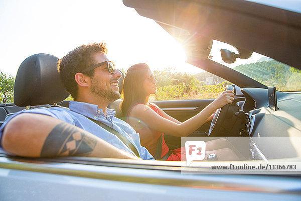 Junges Paar fährt auf sonnenbeschienener Landstraße im Cabriolet  Mallorca  Spanien