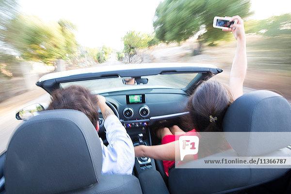 Rückansicht eines jungen Paares  das sich beim Fahren auf einer Landstraße im Cabriolet selbstständig macht  Mallorca  Spanien