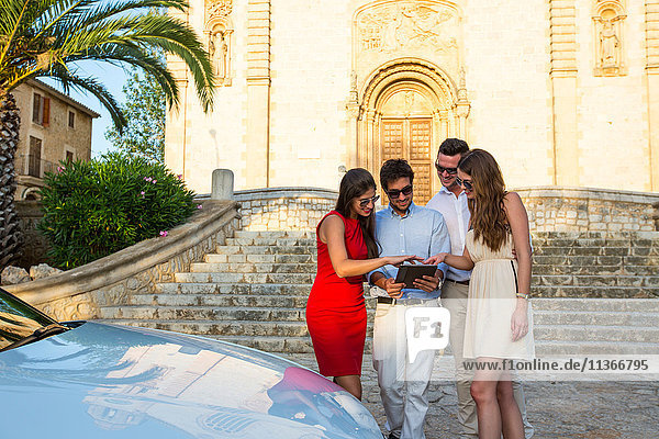 Two tourist couples looking at digital tablet by church  Calvia  Majorca  Spain