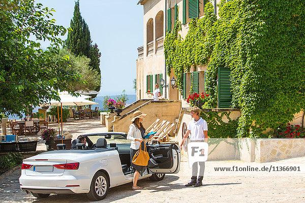 Pförtner begrüßt Paar  das im Cabriolet im Boutique-Hotel ankommt  Mallorca  Spanien