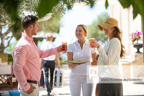 Boutique-Hotel-Kellnerin empfängt Ehepaar mit Getränken  Mallorca  Spanien