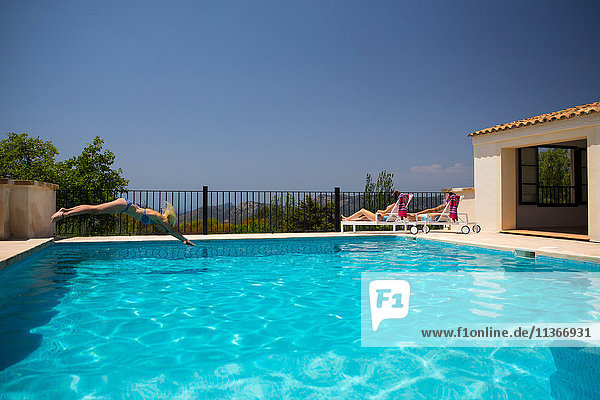 Young woman diving into boutique hotel swimming pool  Majorca  Spain