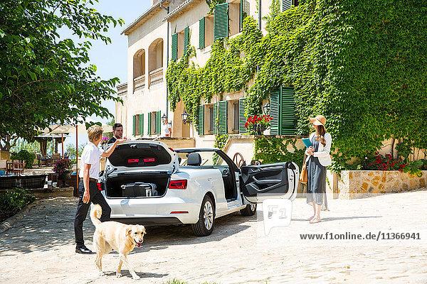 Boutique-Hotel-Portier holt Gepäck für ein Paar,  das mit einem Cabrio ankommt,  Mallorca,  Spanien