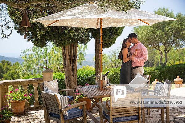 Romantisches Paar küsst sich auf der Terrasse eines Boutique-Hotels  Mallorca  Spanien