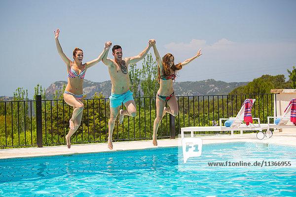 Junge Frauen und Männer springen gemeinsam in den Swimmingpool eines Boutique-Hotels  Mallorca  Spanien
