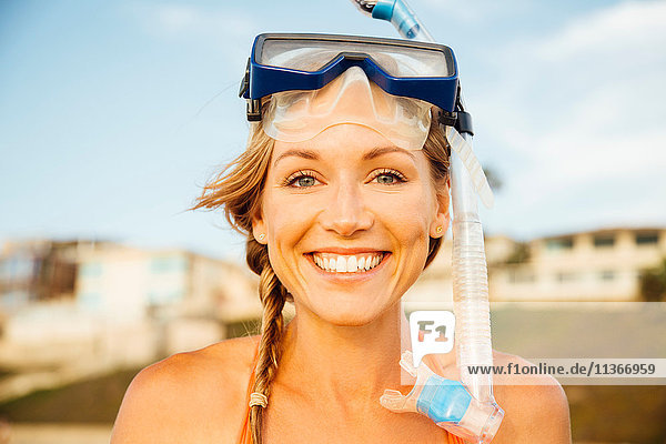 Portrait of woman wearing snorkel looking at camera smiling