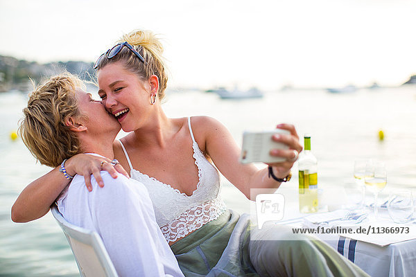 Junges Paar lacht und nimmt Selbstgefälligkeit im Hafenrestaurant  Mallorca  Spanien