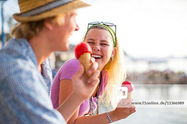 Junges Paar lacht und isst Eistüten am Wasser  Mallorca  Spanien