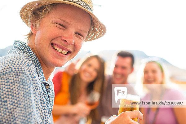 Porträt eines jungen Mannes mit erwachsenen Freunden in einem Restaurant am Wasser  Mallorca  Spanien