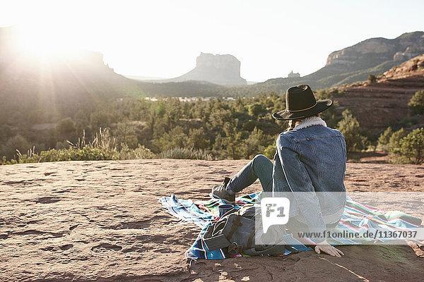 Frau sitzt auf einer Decke in der Wüste und schaut auf Ansicht  Rückansicht  Sedona  Arizona  USA