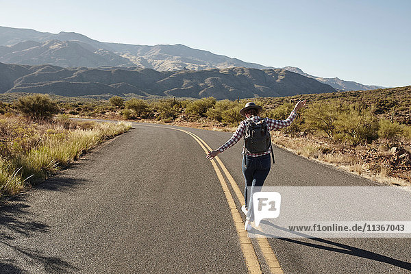 Woman walking along road markings of desert road  rear view  Sedona  Arizona  USA