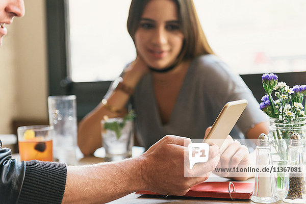 Young couple sitting in restaurant  looking at smartphone