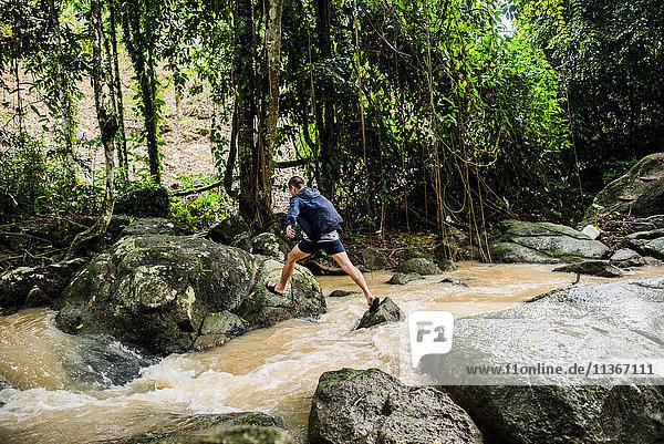 Young man crossing stream  Secret Buddha Garden  Koh Samui  Thailand