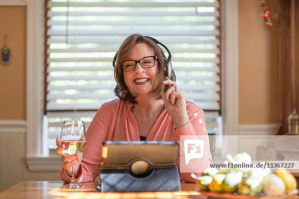 Seniorin am Küchentisch beim Kopfhörer hören