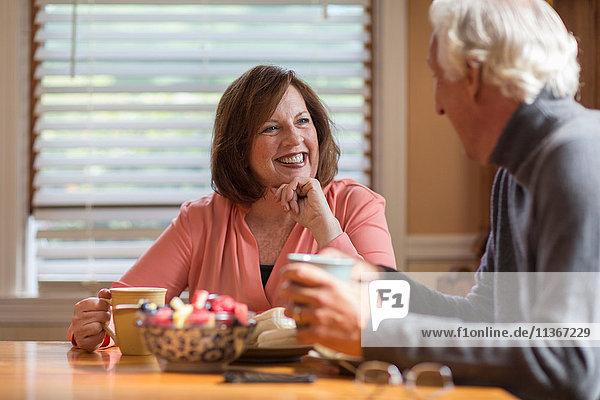 Seniorenpaar im Gespräch am Küchentisch
