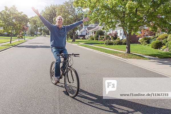Älterer Mann mit erhobenen Händen beim Radfahren entlang einer Vorstadtstraße