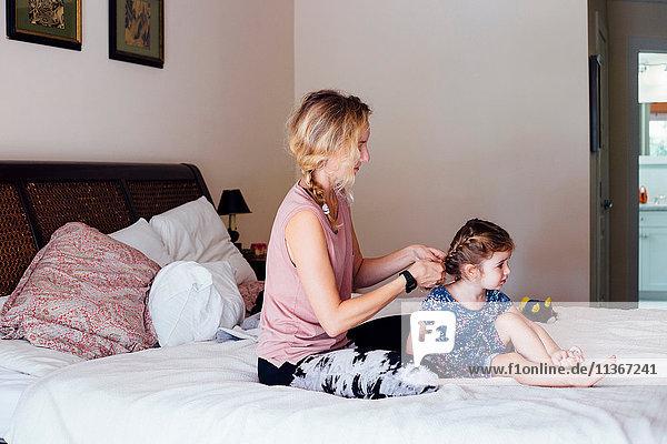 Frau sitzt auf dem Bett und flechtet die Haare der Kleinkind-Tochter