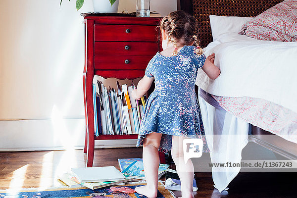 Rear view of female toddler selecting storybook from shelf