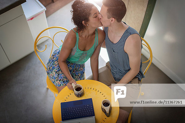 High angle view of romantic young couple kissing at kitchen table