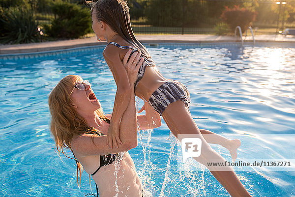Mother and daughter in swimming pool  mother lifting daughter