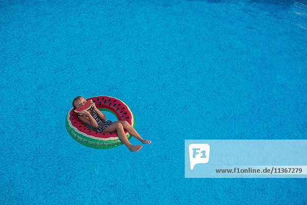 Junges Mädchen im Schwimmbad  entspannt auf aufblasbarem Ring  isst Wassermelone