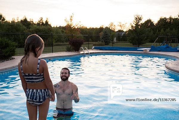 Junges Mädchen steht am Rand eines Swimmingpools  der Vater im Pool ermutigt sie  hineinzuspringen