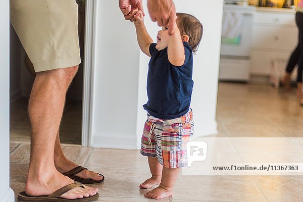 Father holding hands of toddler  guiding him to walk