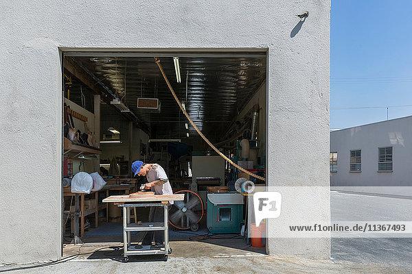 Guitar maker manufacturing guitar outside workshop