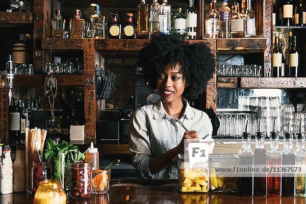 Barkeeper arbeitet hinter der Bar in einer Kneipe